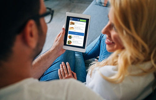 Man and woman on couch looking at mobile phone with Online Ordering app