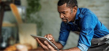 male employee leaning on store counter looking at mobile tablet screen