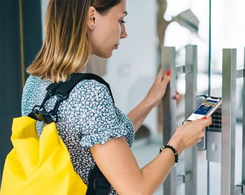 Woman entering door with mobile ID on iPhone